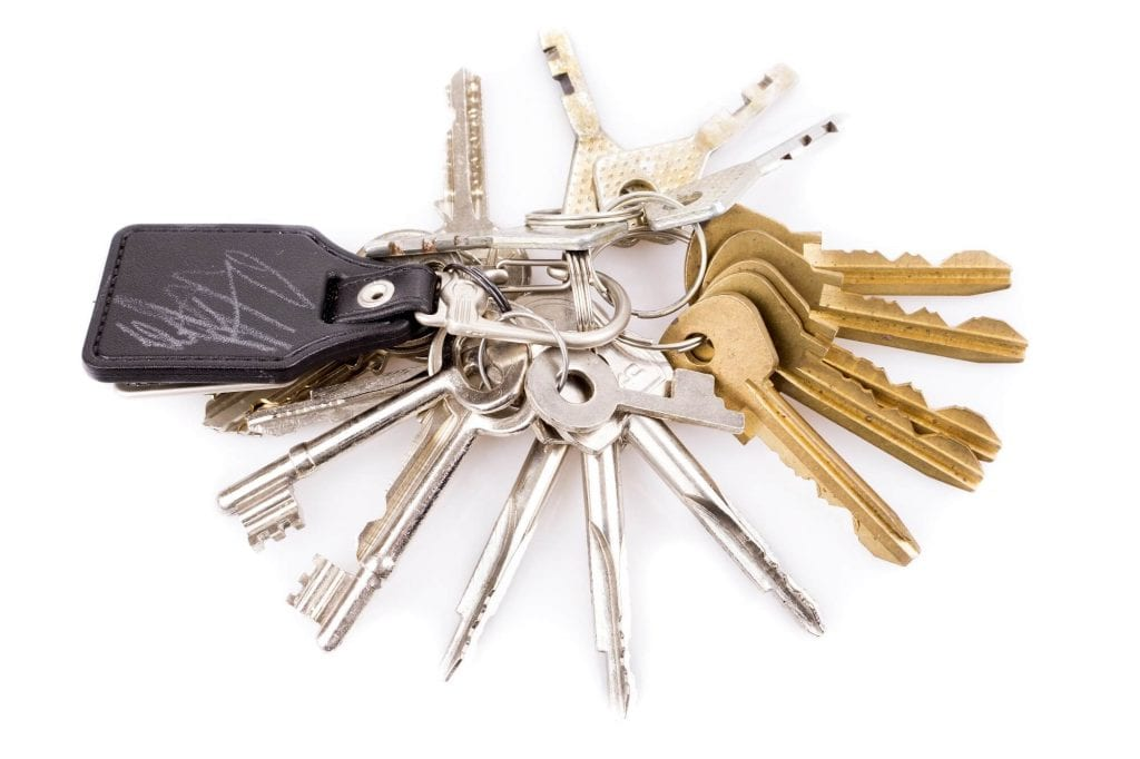 Bunch of keys and leather keychain on white